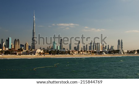 Downtown of Dubai (UAE, United Arab Emirates) in the evening. Beautiful skyline of modern city built in the desert.  Burj Khalifa, the tallest building in world.The view from beach of Persian Gulf.