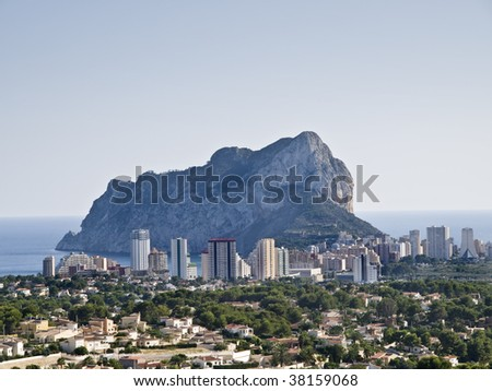 Downtown of the city of Calpe, Costa Blanca - Spain, with the famous mountain called El Peñón de Ifach located behind the buildings - stock photo
