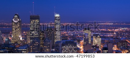 downtown panorama skyline montreal at dusk cityscape with skyscrapers lights on and saint lawrence river and bridge and suburban area in background, the lights are reflecting on the river surface - stock photo