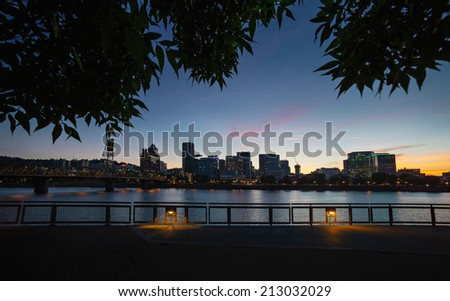 Downtown Portland cityscape during beautiful late sunset framed with tree leaves - stock photo