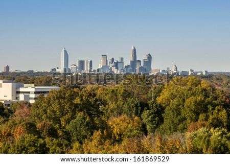 Downtown uptown Charlotte, North Carolina skyline in the distance beyond vibrant fall colored trees  - stock photo