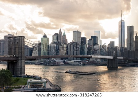 Downtown view of New York at sunset with warm toning and dramatic sky - stock photo