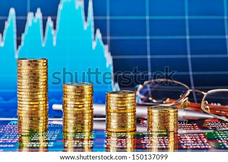 Downtrend financial chart, glasses, pen and stacks of golden coins. Selective focus - stock photo