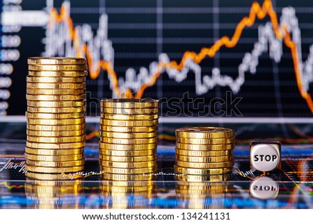 Downtrend financial chart, stacks of golden coins and dices cube with the word STOP. Selective focus - stock photo