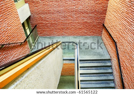 Downward perspective on staircase in a building made of orange red bricks, different materials on all surfaces. - stock photo