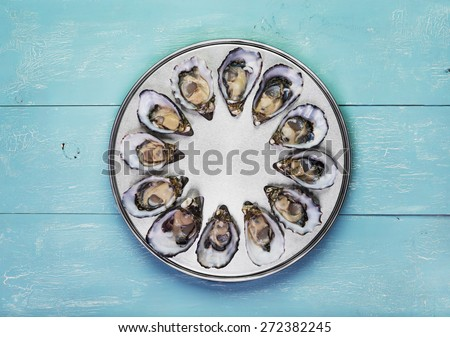 dozen fresh oysters on special cooking and serving metal tray