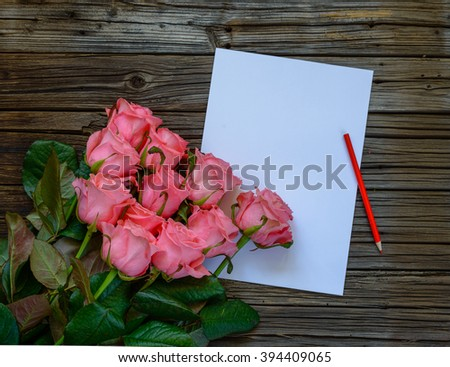 Dozen pink roses on stems beside plain white paper and red colored pencil on a knotted dark wood table - stock photo