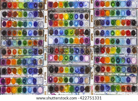 Dozens of well used watercolor pans arranged in a side by side grid displaying a full rainbow spectrum of vivid color - stock photo