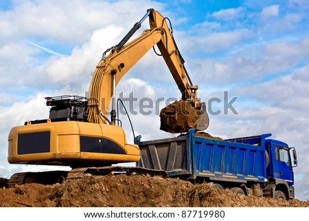 Dozer Backhoe loading soil or sand into Tip Truck - stock photo