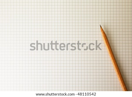 Drafting paper or graph paper with pencil under warm incandescent lighting - stock photo