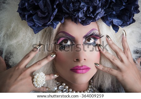 Drag queen with spectacular makeup, glamorous trashy look, posing while using hands and fingers - stock photo