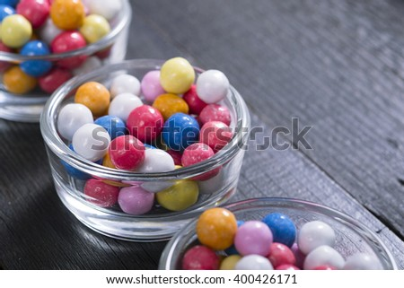 dragees, sugar coated pills at glass dish, on black wood table background