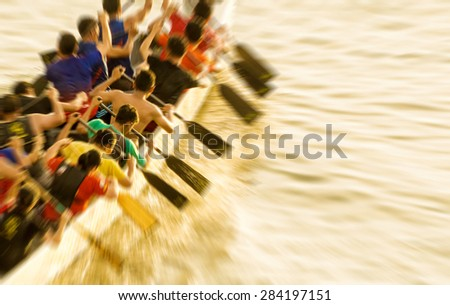 Dragon boat participant practice paddling during sunset golden hour with lens pan-zooming  blur effect. - stock photo