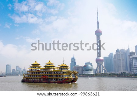 Dragon boat through the Shanghai skyline - stock photo