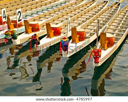 Dragon boats in a warm evening sunlight before the race - stock photo
