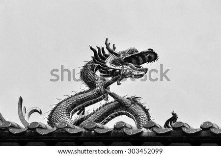 Dragon on the roof of a Chinese temple in Yangon, Myanmar.   Dragon is on the rooftop of the Kheng Hock Keong Buddhist  Temple in China Town Yangon. Monochrome picture. - stock photo