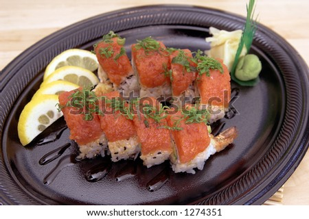 Dragon Roll sushi roll with wasabi and pickled ginger and garnished with chopped chives - stock photo