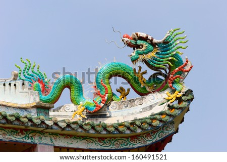 dragon statue on china temple roof with blue sky