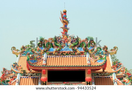 Dragon Statue on Top of Chinese Temple Shrine with blue sky