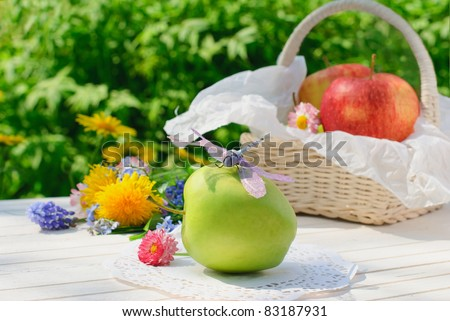 Dragonfly sits on green apple on white garden table in sunny summer day - stock photo