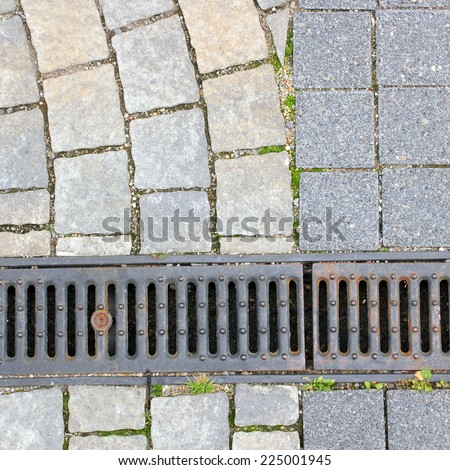 drain and stone pavement on pedestrian urban street - stock photo