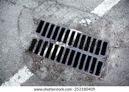 Drain grate with white road marking line on it. - stock photo