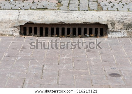 Drain gutter in the road, next to pavement, showing curb - stock photo