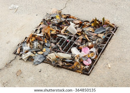 drain lid covered with garbage causing flood  - stock photo