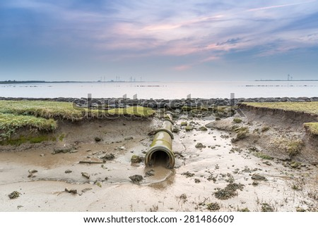 Drain pipe on the coast of the Wadden sea - stock photo