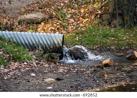 Drainage pipe with water flowing out - stock photo