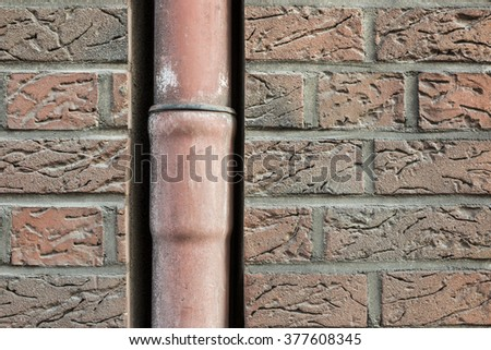 drainpipe in a brick wall - stock photo