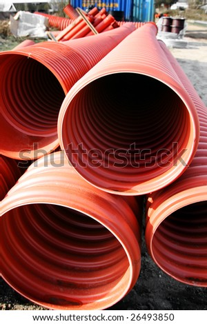 Drainpipes on building site. Red plastic drainage material - stock photo