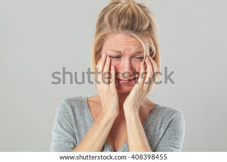 drama concept - childish young blond woman crying with big tears expressing her sorrow and regret, grey background studio - stock photo