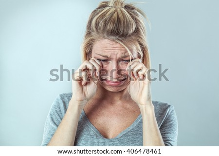 drama concept - desperate young blond woman crying with big tears comforting her break down and sorrow, grey background studio, contrast effects