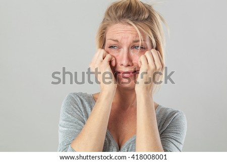 drama concept - upset young blond woman crying with big tears expressing her disappointment and sadness, grey background studio - stock photo