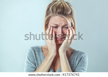 drama concept - upset young blond woman crying with big tears expressing her sorrow and regret, grey background studio, contrast effects - stock photo