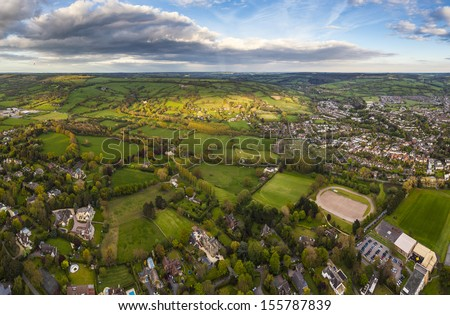 Dramatic aerial view of idyllic rolling patchwork farmland and houses with pretty wooded boundaries, lit in warm early evening sunshine in the heart of the Cotswolds, England, UK. - stock photo