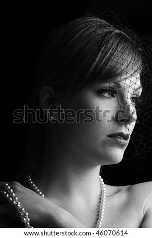 dramatic and low key black and white picture of a beautiful woman with a net veil
