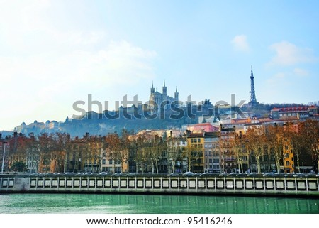Dramatic and scenic sunrise over the river Saone in Lyon, France, with the Notre-Dame de Fourviere basilica and eiffel tower replica in the misty morning background. - stock photo