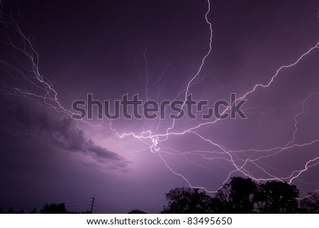 Dramatic and spectacular lightning bolts flash across the night sky illuminating storm clouds over Central Indiana in the American Midwest. - stock photo