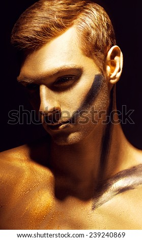 Dramatic art portrait of man in bronze paint on his body and gold makeup.  Close up portrait of a man with black mark on the face. - stock photo
