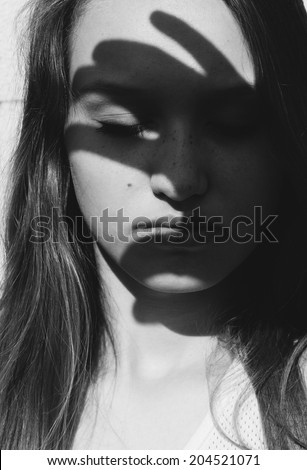 Dramatic artistic portrait of an attractive long haired young woman with downcast eyes and a serious expression casting a dark shadow silhouette of splayed fingers across her face in the sunshine - stock photo