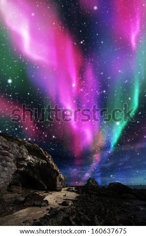dramatic aurora borealis above the rock. - stock photo
