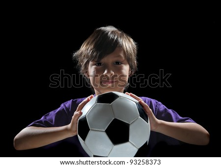 Dramatic back-lit boy with soccer ball on black background - stock photo
