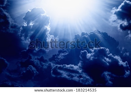 Dramatic background - dark blue sky with bright sun, light from heaven - stock photo