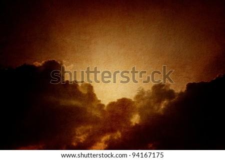 Dramatic background - dark sky, bright sun on textured paper - stock photo
