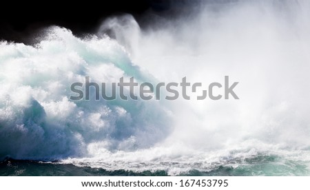Dramatic background image of crashing wall of flood water stream breaking with flying spray - stock photo