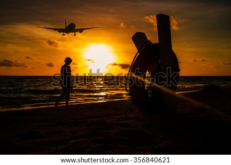 Dramatic beach sunset and airplane lending with person walking along see