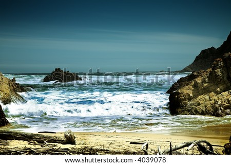 Dramatic beach with foaming ocean waves - stock photo