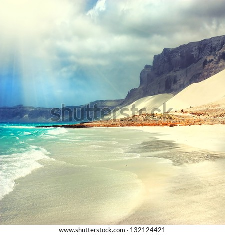 dramatic beach with sunlight and wave at beautiful sandy beach - stock photo